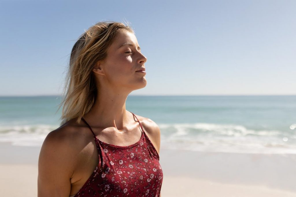 Jeune femme respirant à plein poumons